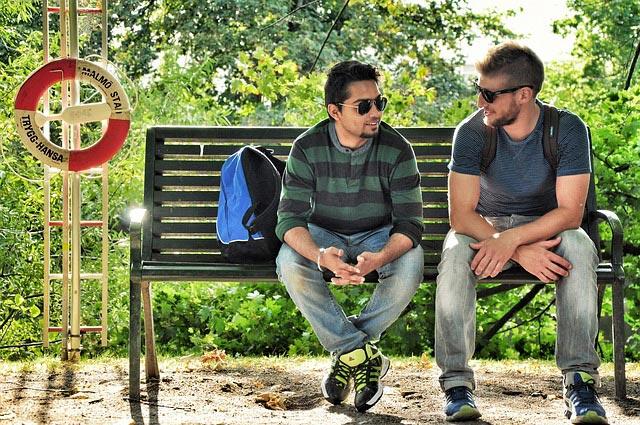 zwei Jugendliche auf einer Bank mit Kommunikation beschäftigt